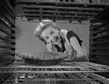 Женщина, глядя на пирог в духовке