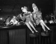 Женщины, сидя на барной стойке